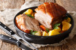 Leinwandbild Motiv German recipe crispy pork served with vegetables and gravy close-up in a pan on the table. horizontal