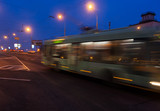 The motion of a blurred trolleybus in the street in the evening.