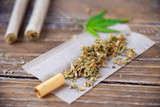 Cannabis joints with rolling paper over wood background - 232035732