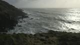 Cinematic tilt up wide shot of waves in Cornwall, England - 232039733