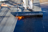 Worker preparing part of bitumen roofing felt roll for melting by gas heater torch flame - 232041570