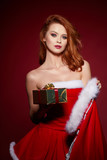Happy excited young woman in santa claus costume with gift box over red  background - 232059905