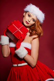 Happy excited young woman in santa claus costume with gift box over red  background - 232059951