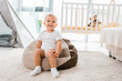 adorable smiling toddler sitting on bean bag chair  in nursery room