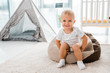 adorable smiling toddler sitting on bean bag chair and looking at camera in nursery room