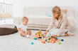 adorable toddler playing with colorful cubes and mother in nursery room