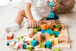 cropped view of adorable toddler playing with colorful cubes