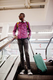 African american man in checkered shirt, sunglasses and jeans with suitcase and backpack. Black man traveler on escalator. - 232062362