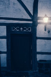 Illuminated lantern at door of old country house. - 232063100