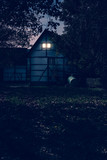 Historic country house with illuminated window at dusk. - 232063115