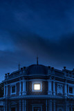 Historical mansion with illuminated window under dark sky at dusk. - 232063188