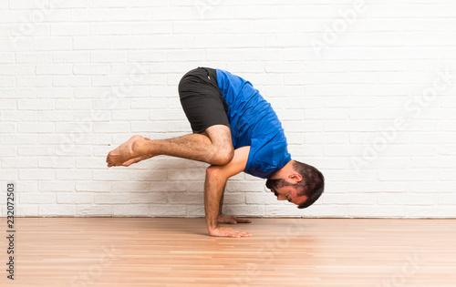 Leinwanddruck Bild Man doing yoga exercises indoors