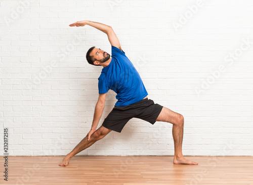Leinwandbild Motiv Man doing yoga exercises indoors