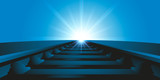 Vue au ras du sol et en perspective de rails de chemin de fer en direction du soleil qui se lève à l'horizon.  - 232073778