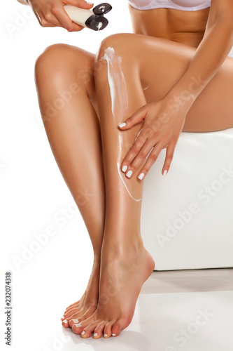 Leinwanddruck Bild woman applying lotion on her legs on white background