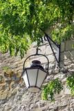 Vieille lanterne accrochée à un vieux mur en pierre sous un arbre vert, Beaugency, ville du Val de Loire, département du Loiret, France - 232077548