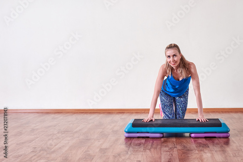 Sticker Young sportive woman exercising in gym using step platform, copy space.