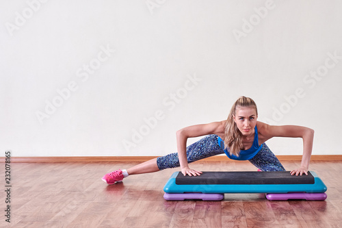Wall mural Young sportive woman exercising in gym using step platform, copy space.