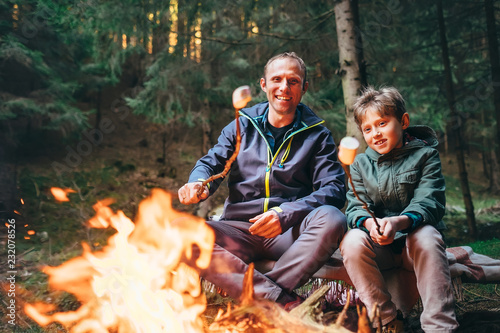 Leinwanddruck Bild Father and son roast marshmallow candies on campfire in forest. Family relationship concept image