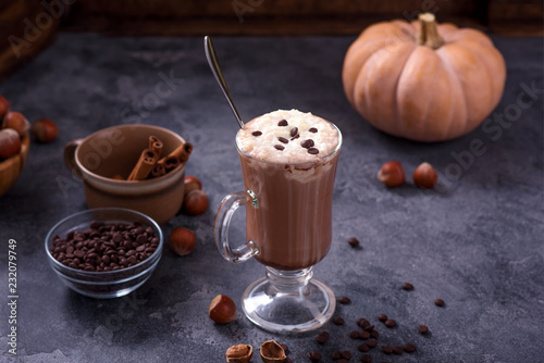 Hot chocolate drink with pumpkin and nuts on dark background