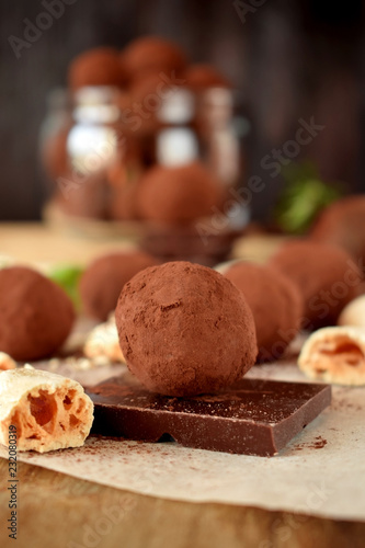 Wall mural Chocolate truffles sprinkled with cocoa powder and meringues