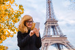 Girl using cellphone with Paris city background and Eiffel tower.