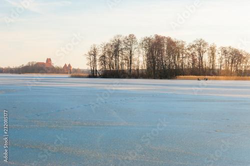 Foto Murales Fishermen on frozen lake Galve with Trakai Castle on background