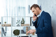 serious businessman in suit talking on smartphone and gesturing by hand in modern office