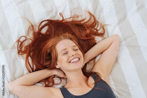 Leinwandbild Motiv Happy healthy young redhead woman in bed