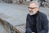 trendy senior man seated on a bench in the street - 232094583