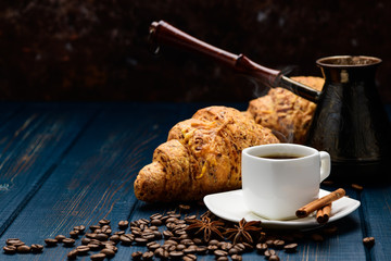 coffee pours into a Cup on a blue wooden table with coffee beans and a croissant