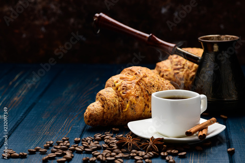 Poster coffee pours into a Cup on a blue wooden table with coffee beans and a croissant