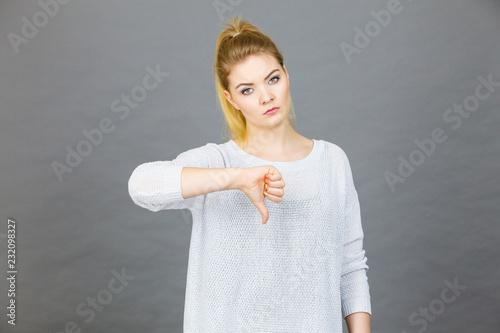 Smutna kobieta pokazuje kciuka puszka gest