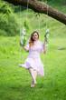 Leinwandbild Motiv Beautiful girl in summer dress rides on the swing.
