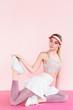 young stylish female athlete in visor hat exercising on pink