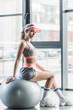 sportswoman in visor hat sitting on grey fitness ball at gym