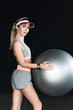young female athlete in visor hat with fitness ball on black