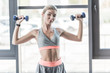 pretty young woman exercising with dumbbells at gym