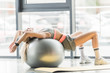 selective focus of young female athlete doing exercise with fitness ball at gym
