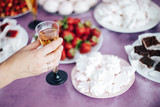 women's hand holding a glass of champagne on the background of the festive table - 232111775
