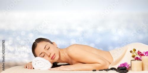 Leinwanddruck Bild Beautiful young woman relaxing with stone massage at beauty spa