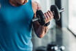 close up of young sportsman exercising with dumbbell in gym