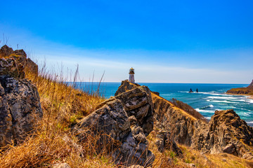 Sunny day on the coast of the Japanese Sea. Coastline cliffs and lighthouse. © Andrey