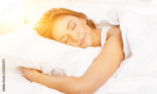 Leinwanddruck Bild Young woman  sleeping on the white linen in bed at home