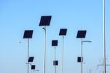 Street lighting works from solar panels, blue sky background. Before electricity transmission pylon. - 232126316