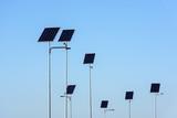 Street lighting works from solar panels, blue sky background. Before electricity transmission pylon. - 232126323