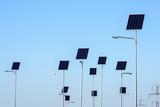 Street lighting works from solar panels, blue sky background. Before electricity transmission pylon. - 232126546