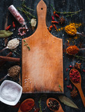 Spices and herbs with cutting board on dark background, top view, copy space - 232133575