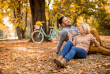 Young couple sitting on ground in autumn park - 232134319