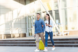 Couple of tourists with yellow suitcase leaving the airport - 232145304